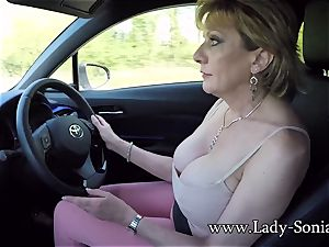 Mature woman Sonia plays with her fun bags while driving